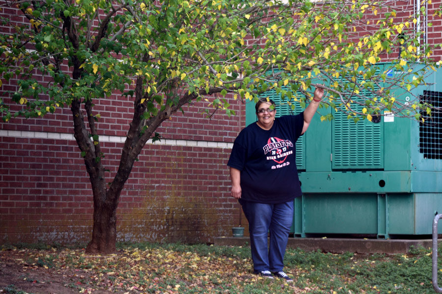 Sandra Gulley standing next to the Rose of Sharon tree she planted 20 years ago.