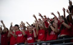 The Ryan High School student section, Code Red, cheers on the varsity football team during kickoff of the game against Mesquite Poteet High School.